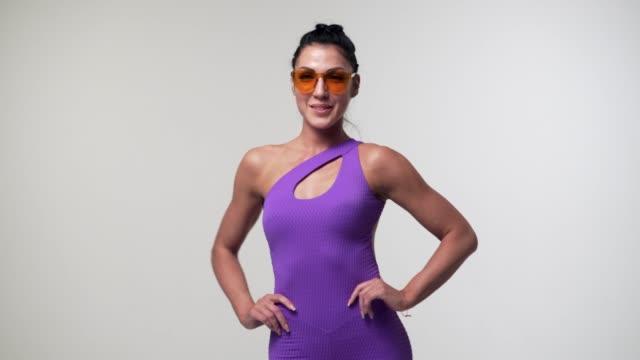 beautiful woman posing in bodysuit at studio - mani sui fianchi video stock e b–roll