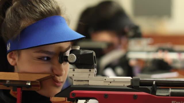 vacker kvinna öva sportskytte - tävlingsidrott bildbanksvideor och videomaterial från bakom kulisserna