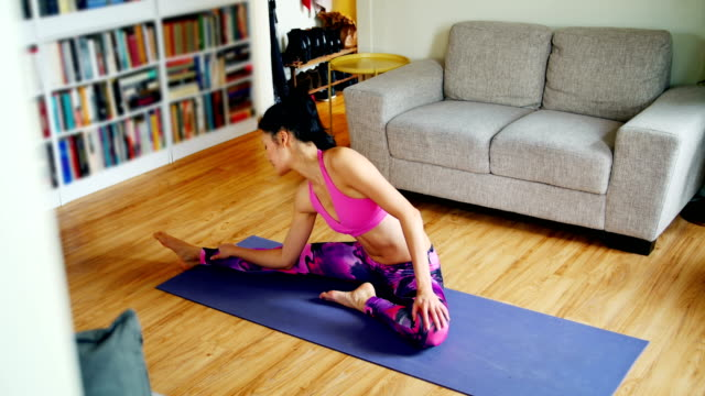 Beautiful woman practicing yoga in living room video