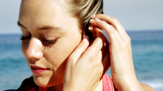 Beautiful woman putting earphones in her ear before jogging video