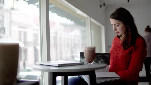 Beautiful woman reading newspaper, drinking coffee in cafe video