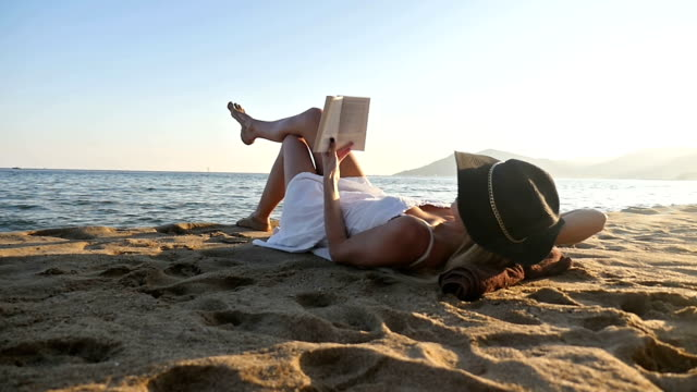 Beautiful woman reading on beach Hd slow motion video of young woman lying on beach and reading book at the edge of Mediterranean sea in south of France. Attractive blond girl wearing big sunhat and white dress. Beautiful woman enjoying her vacation and relaxing. Sunset time, space for copy sunbathing stock videos & royalty-free footage