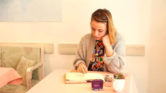 Beautiful woman reading the menu Beautiful young woman reading the menu in a cafe served coffee menu stock videos & royalty-free footage