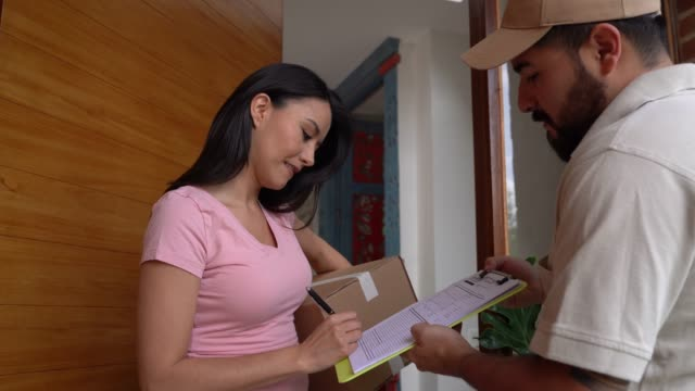 Beautiful woman receiving a box from postal worker and signing off a sheet smiling