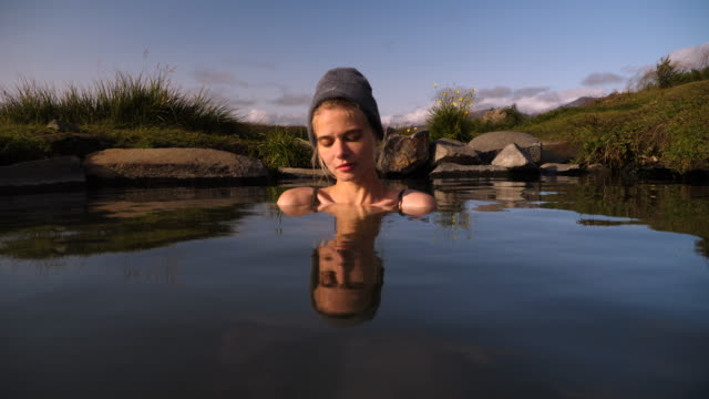 Beautiful woman resting in hot natural pool in Iceland - video