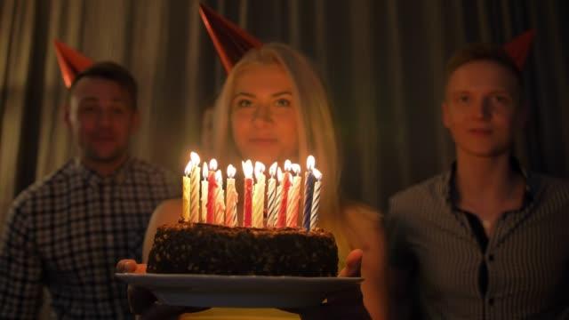 schöne frau aktien geburtstagsfeier mit freunden gesammelt ausblasen der kerzen auf kuchen - geburtstagstorte stock-videos und b-roll-filmmaterial