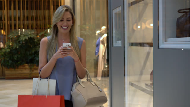vídeos de stock e filmes b-roll de beautiful woman shopping in the mall while texting and looking at retail displays - online shopping
