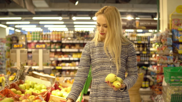 Beautiful woman shopping vegetables and fruits in supermarket.