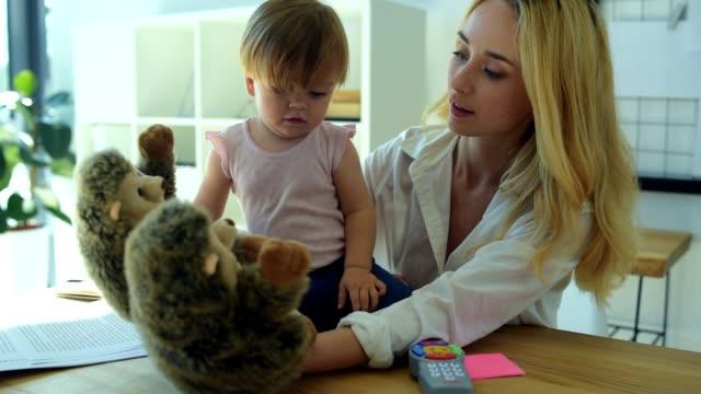 schöne frau zeigt verschiedene spielzeuge für das kind - neues zuhause stock-videos und b-roll-filmmaterial