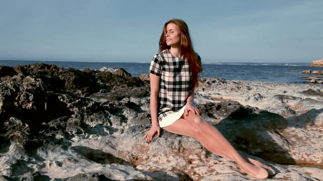 beautiful woman sits on the rocks oceanfront video