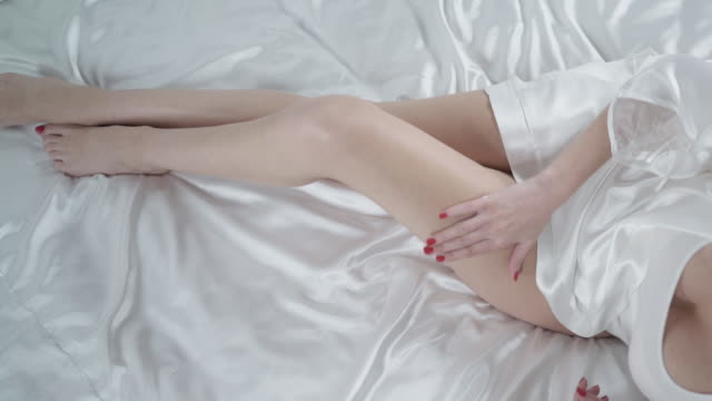 Beautiful woman sitting on bed and applying cream on smooth leg. Legs skin care. video