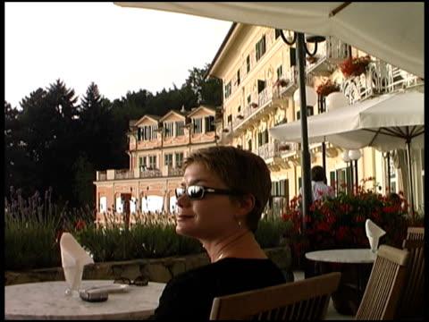 vidéos et rushes de belle femme assis à l'extérieur de l'hôtel, la villa, immobilier, maison, maison - une seule femme d'âge mûr
