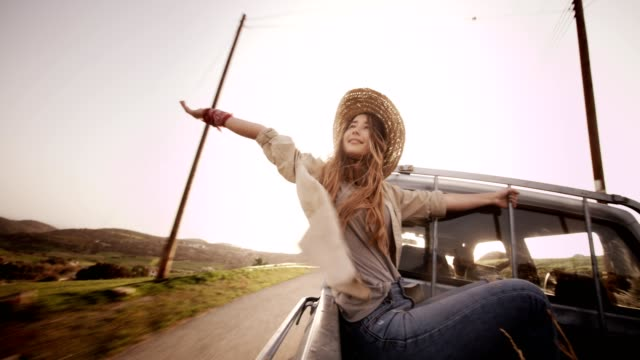 Beautiful woman sitting with outstretched arms in a pick-up truck Girl with open arms travelling in the country in the back of a pick-up truck cowgirl stock videos & royalty-free footage
