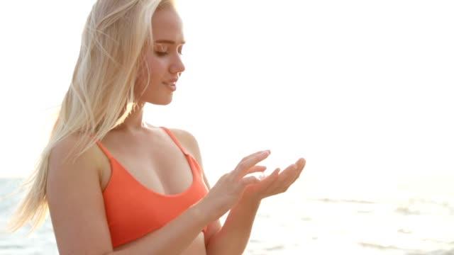 vídeos de stock e filmes b-roll de beautiful woman smears face sunscreen at the beach for protection - protetor solar