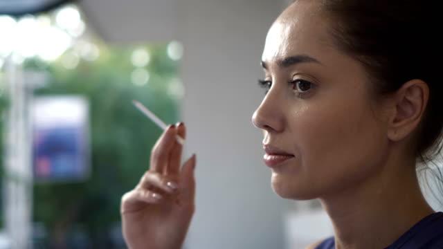 Beautiful woman smoking a cigarette outdoors close up