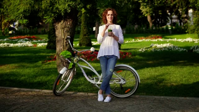 beautiful woman standing in the city park near her city bicycle with flowers in its basket and drinking green detox smoothie. healthy lifestyle - sok filmów i materiałów b-roll