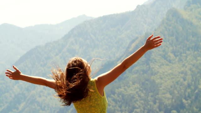 산 꼭대기에 서 있는 고 손을 뻗어 아름 다운 여자 - mountain top 스톡 비디오 및 b-롤 화면