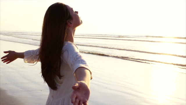 Beautiful woman standing with arms outstretched on shore Tilt up slow motion video of woman standing on wet shore. Side view of carefree female with arms outstretched and eyes closed. Woman in white sundress enjoying nature on beach during sunset. eyes closed stock videos & royalty-free footage