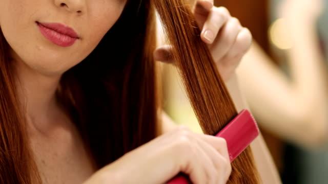 vacker kvinna uträtning friska röda hår med järn plattång - järn bildbanksvideor och videomaterial från bakom kulisserna