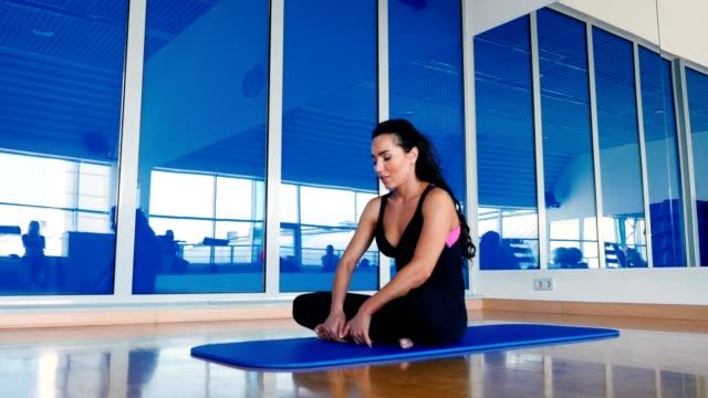 beautiful woman stretching her back in lotus position on the mat in the gym - gambe incrociate video stock e b–roll