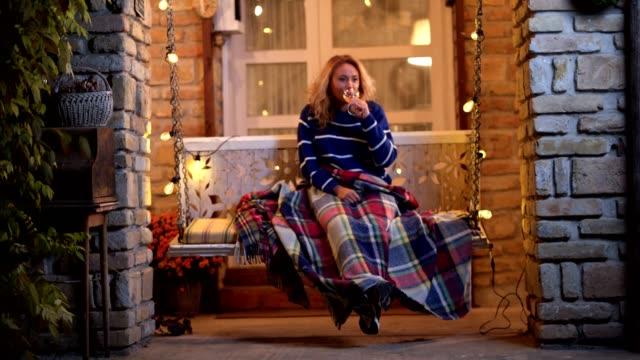 beautiful woman swinging and drinking wine - portico video stock e b–roll