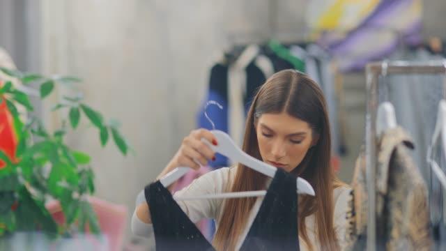 vídeos de stock, filmes e b-roll de a mulher bonita tira seu vestido do gancho e tenta-se em si mesma uma escolha da roupa em um boutique da forma. mulher feliz em uma loja de roupa. vista do retrato. - boutique