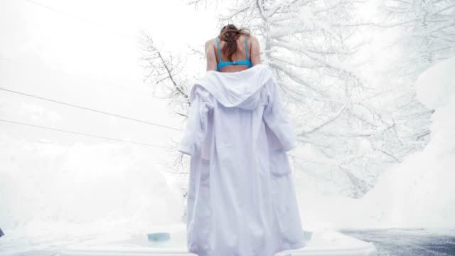 a beautiful woman takes off her white bathrobe and enters the hot tub in the middle of nature as the snow falls from the sky. - bikini video stock e b–roll