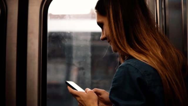 Beautiful woman taking a subway in Chicago, USA. Attractive female using smartphone while train is moving on sunset