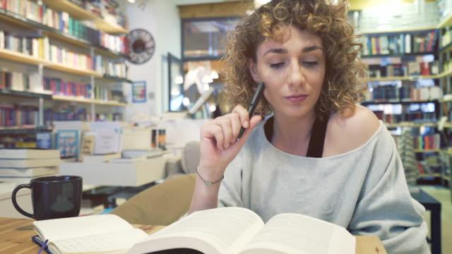 stockvideo's en b-roll-footage met mooie vrouw het maken van notities in een bibliotheek. - blond curly hair