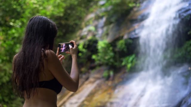 Beautiful woman taking photos at the waterfall