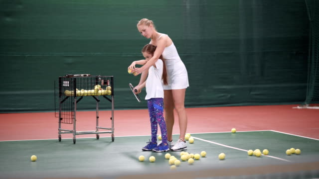 Beautiful woman tennis coach teaching little girl how to play tennis video