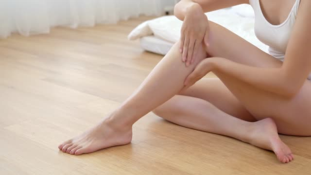 Beautiful woman touches her legs Beautiful woman touches her legs sitting on wooden floor in the bedroom. Body care concept. indulgence stock videos & royalty-free footage