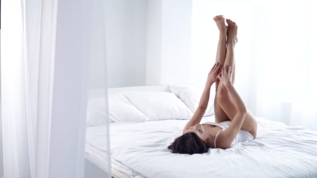 beautiful woman touching long leg skin and lying on bed - depilacja filmów i materiałów b-roll
