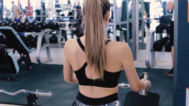 ジムでの美しい女性のトレーニングワークアウト。ヘルスケア、運動、スポーツのコンセプト。 - 機械類点の映像素材/bロール