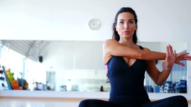 vacker kvinna tränar flexibiliteten på mattan i gymmet - korslagda ben bildbanksvideor och videomaterial från bakom kulisserna