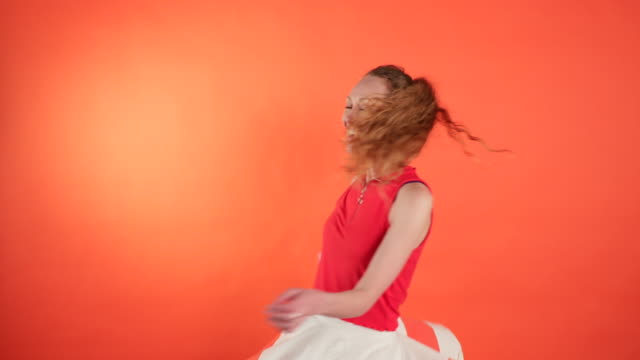 Beautiful Woman Twirling Around Portrait of a woman twirling around, smiling at the camera. She is standing in front of an orange background. background color stock videos & royalty-free footage