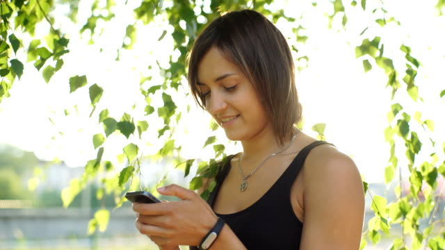 beautiful woman typing a message on your phone in the Park video