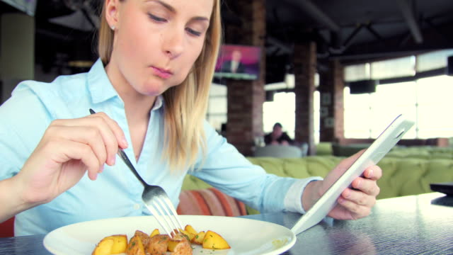 Beautiful woman using ipad tablet computer touchscreen in cafe video