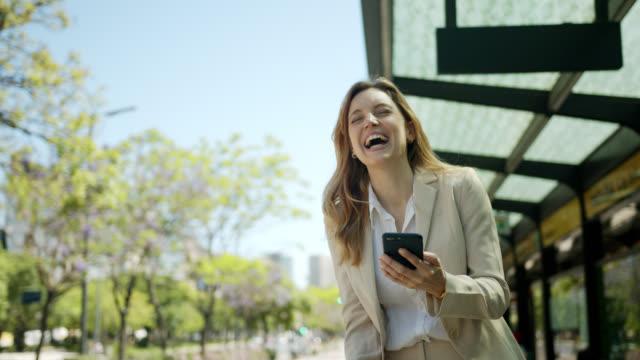 schöne frau wartet auf den bus, während sie etwas lustiges auf dem smartphone liest und kaffee trinkt - geschäftsreise stock-videos und b-roll-filmmaterial