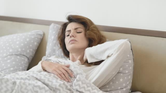 vídeos y material grabado en eventos de stock de hermosa mujer despertando en la cama por la mañana. mujer enferma masajeando el cuello. - almohada