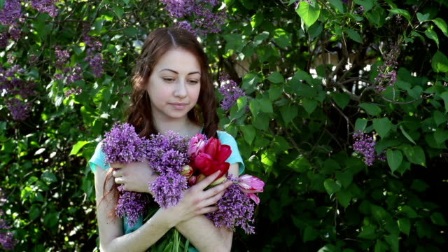 beautiful woman walking in spring park with a bouquet of lilac
