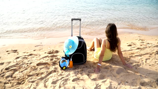 Beautiful woman walking with a suitcase on the sunny beach video