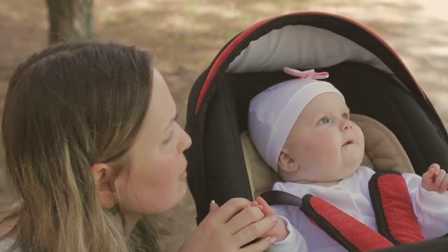 vídeos de stock, filmes e b-roll de linda mulher caminhando com sua filha e empurrando o carrinho de passeio no parque - condado de pitkin