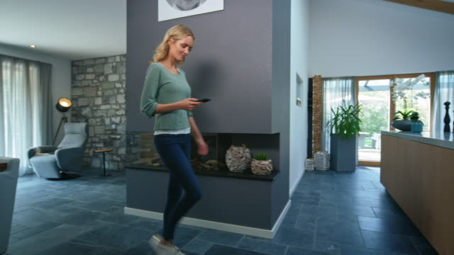 Beautiful woman walking with smart phone at home