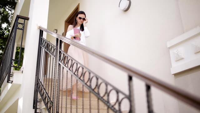 vidéos et rushes de une belle femme se promène dans les escaliers avec une tablette dans les mains - extérieurs d écoles