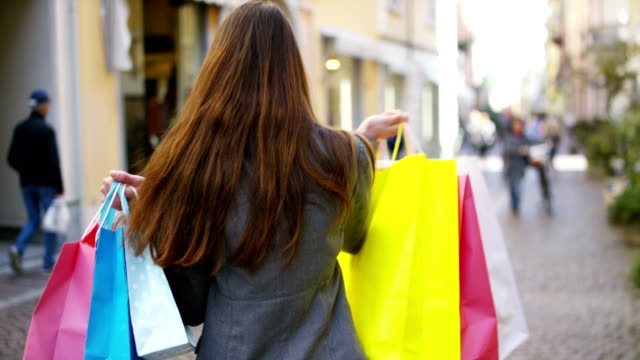A beautiful woman walks through the city on shopping, she is very happy of purchases in the period sales.