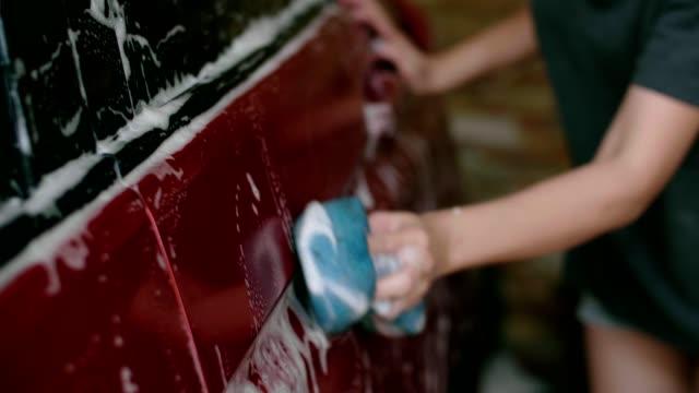 Beautiful woman washing her car