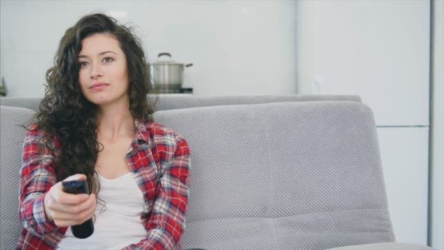 美しい女性はテレビを見て、ソファに座って、彼の手にリモコンを保持しています。 - 人里離れた点の映像素材/bロール