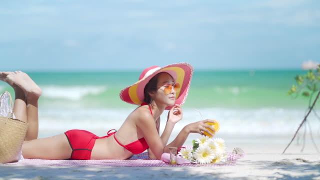 a beautiful woman wearing a red bikini sitting on the beach, koh samed in thailand,drinking orange juice. - tropischer cocktail stock-videos und b-roll-filmmaterial