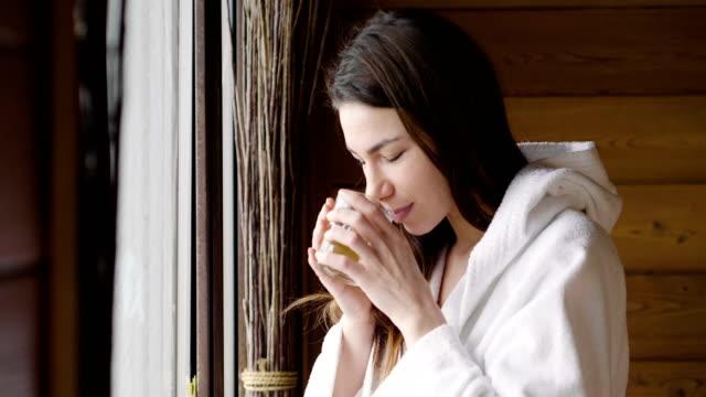eine schöne frau trägt einen weißen bademantel und trinken heißen tee oder kräutertee ausschau. die frau entspannt und denkt wie sie blickt. - sauna und nassmassage stock-videos und b-roll-filmmaterial